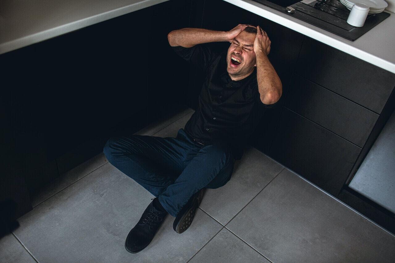 Homem sentado no chão com as mãos na cabeça gritando