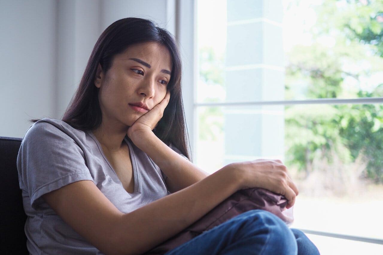 mulher sentada perto da janela aparentando tristeza