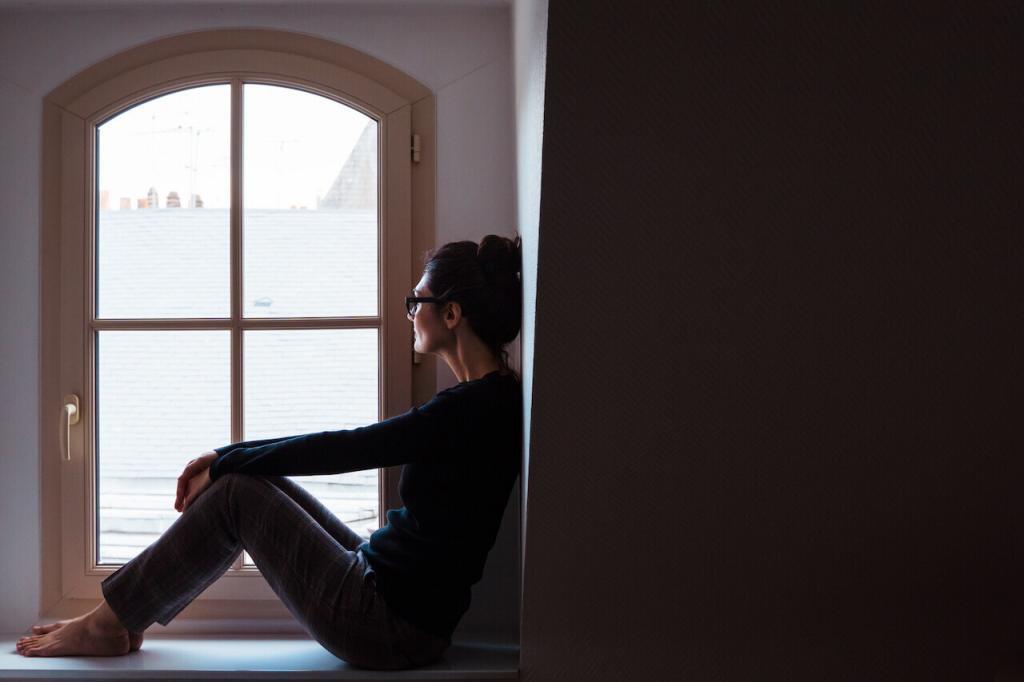 mulher sentada em frente a uma janela observando uma paisagem nevada.