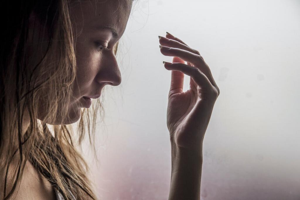 Mulher com a mão em frente ao rosto contra um fundo cinza embaçado