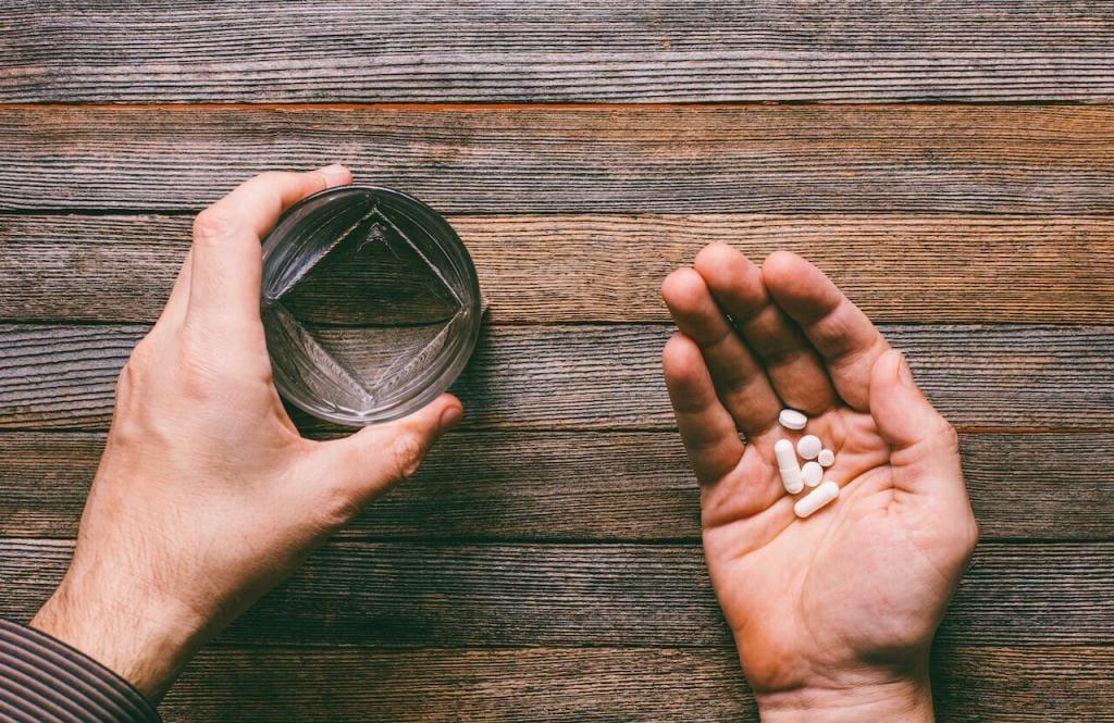 uma mão segurando alguns comprimidos e outra um copo de agua.